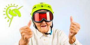 "aging gracefully: elderly woman wearing bright green helmet, amber tinted ski google and holding a ""2 thumbs up"" expression"