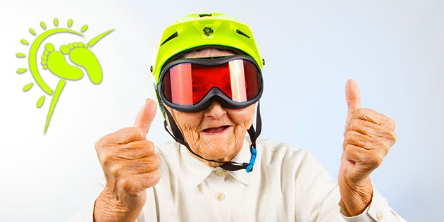 "elderly woman wearing bright green helmet, amber tinted ski google and holding a ""2 thumbs up"" expression"