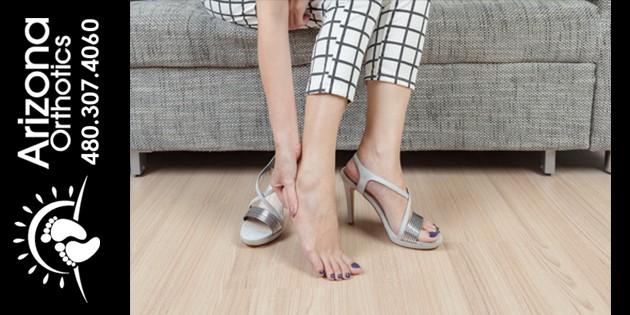 Woman holding aching heel