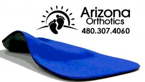 Off-set front view left custom foot orthotic with a blue ultra suede topcover