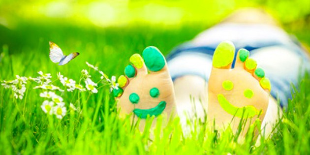 lying down in grass with feet highlighted and painted with a happy face