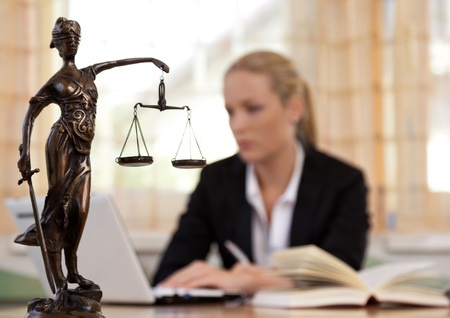 a young lawyer sitting at her desk with the scales of justice on top the main focus