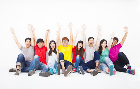 group of happy people with hands held up high in air