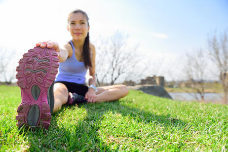 woman stretching her foot sitting outdoors on grass