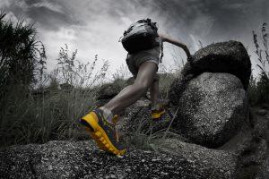 hiker climbing over rocks