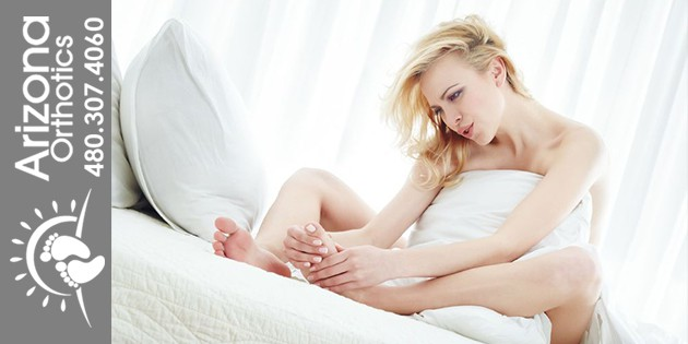 woman in bed looking at her foot
