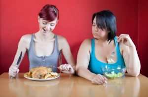 two women sitting at table eating