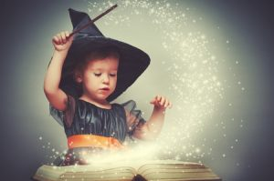girl in Halloween costume performing magic holding a wand with sparkly glitter flying up from her book.
