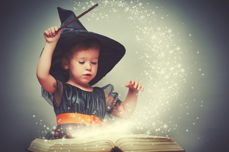 girl in witch costume performing magic