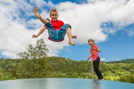 children jumping on trampoline with cloudy blue sky background