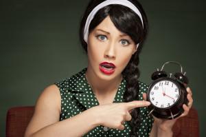 Retro housewife holding an alarm clock