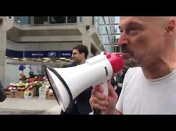 Damon Lenszner shouts at Chris Williamson over a megaphone