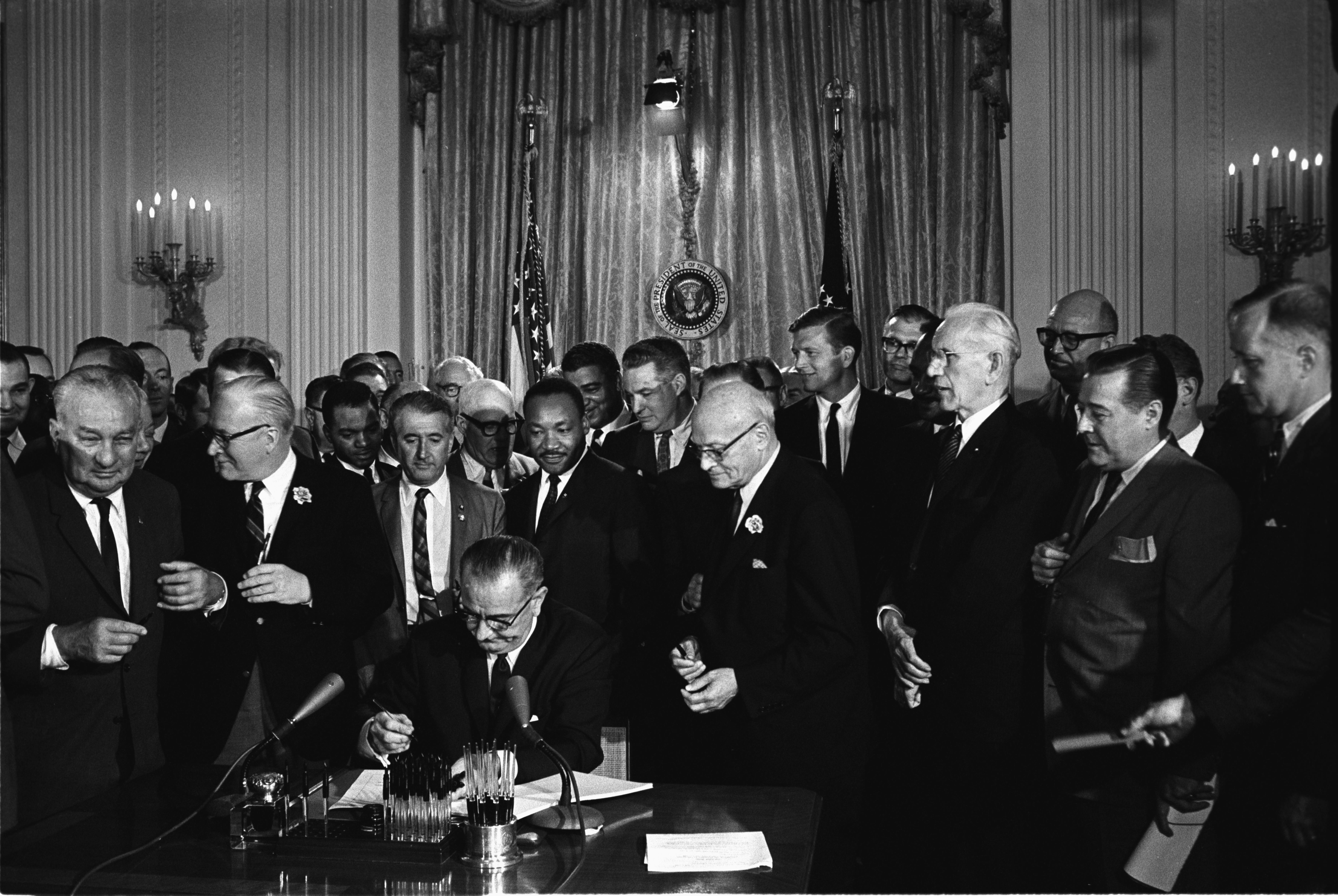 President Johnson signs the Civil Rights Act of 1964. Among the guests behind him is Martin Luther King.