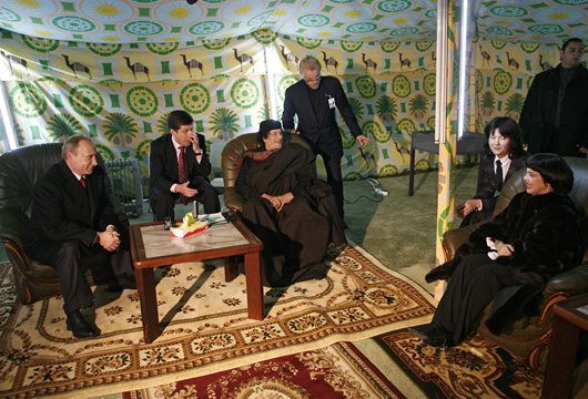 During his 2008 visit to Russia, Gaddafi pitched his Bedouin tent in the grounds of the Moscow Kremlin. Here he is joined by Russian Prime Minister Vladimir Putin and French singer Mireille Mathieu.