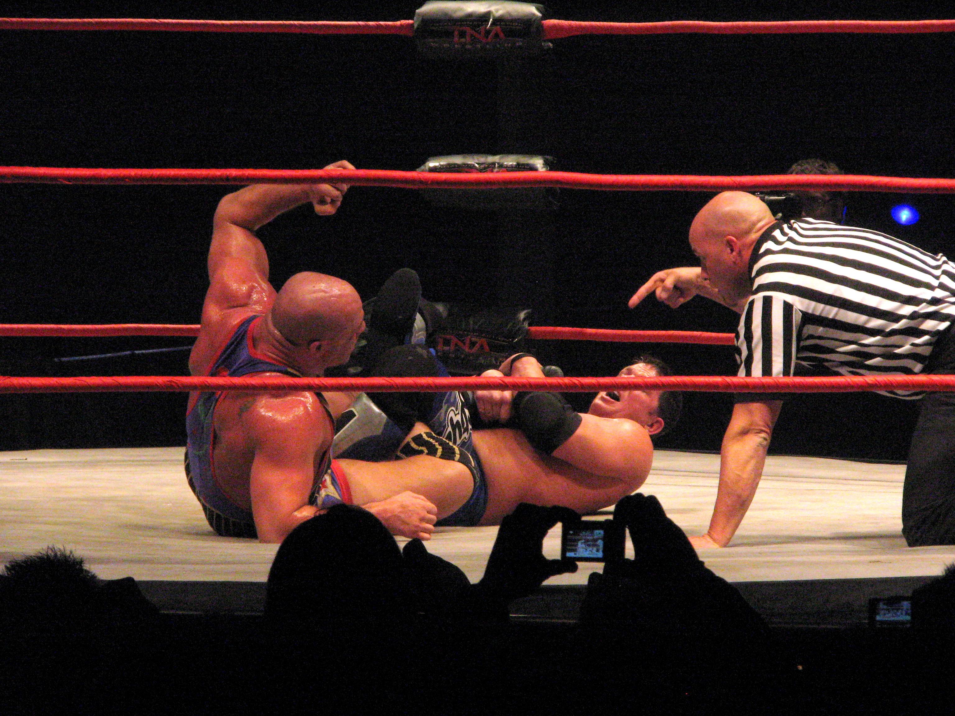 Styles applying a figure-four leglock on Kurt Angle.