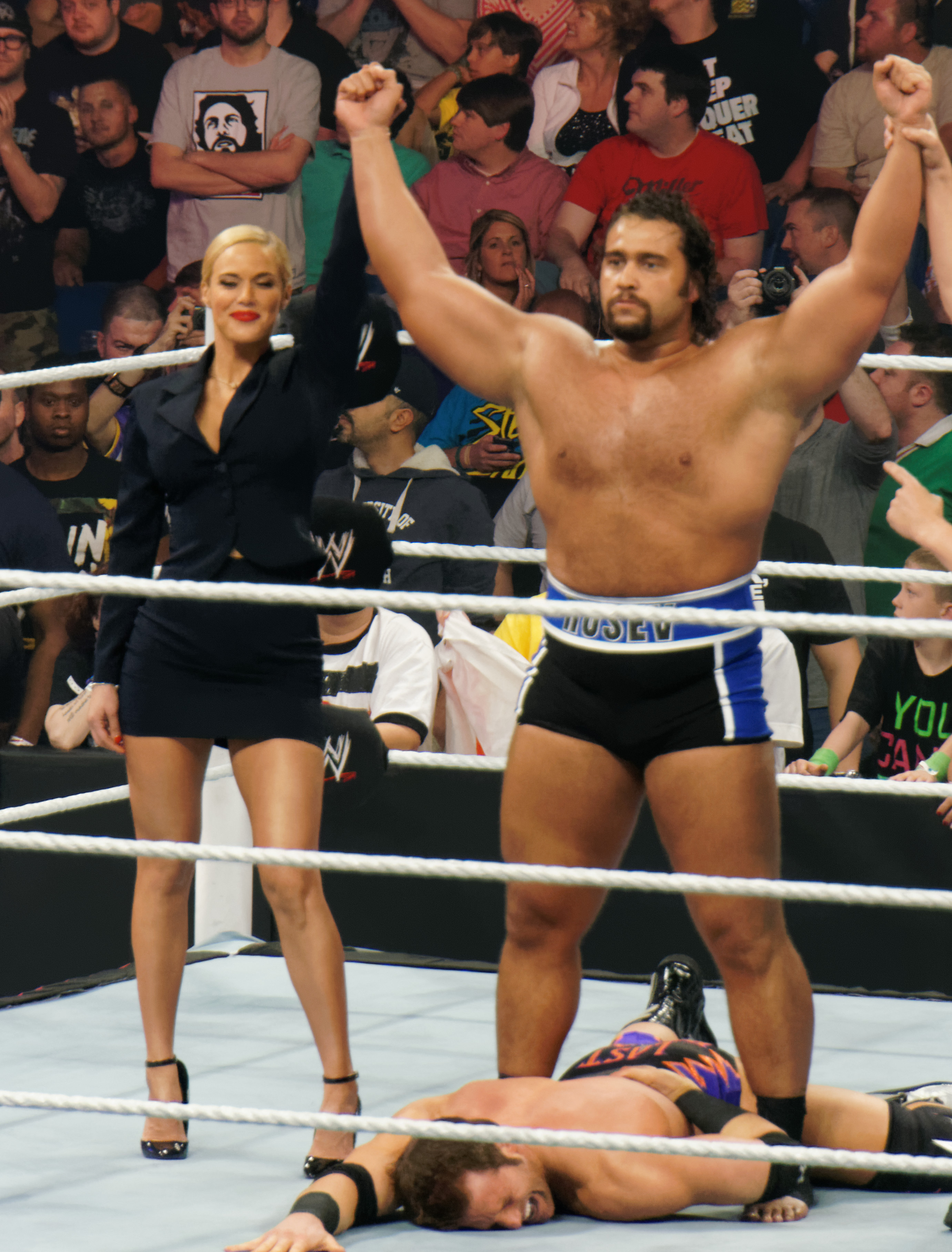 Lana (left) celebrating a win along Alexander Rusev at a Raw event in April 2014