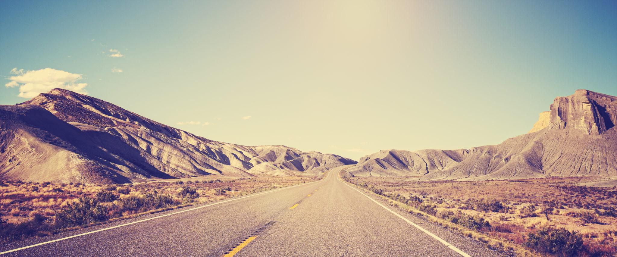 Vintage toned panoramic photo of desert road, Utah, USA.