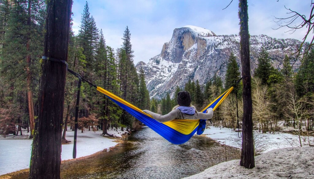 level hammock tip #5 Jess hanging out in a golden state serac camping hammock while enjoying a view of half dome in yosemite national park