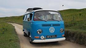 Blue camper van firt road grassy hill h article