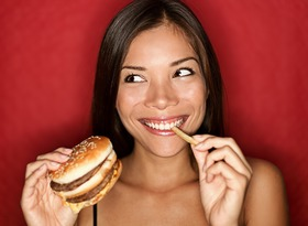 Woman eating burger and fries article
