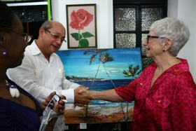 H.e. francisco fern%c3%a1ndez pe%c3%b1a  ambassador of cuba greeted by gallery owner  curator and artist darla trotman. barbados today reporter sandra sealy looks on. article