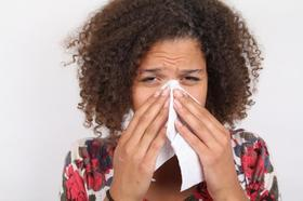 A woman is sneezing into a tissue article