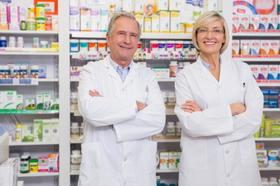 Two pharmacists standing in front of shelves of medicine article