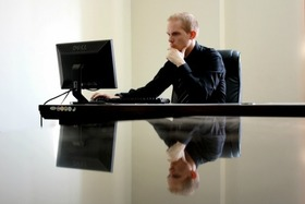 Man behind computer desk 450 article