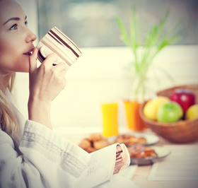 Beautiful calm young woman having morning coffee article