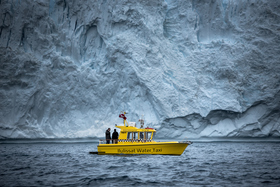 Ilulissat water taxi in front of a big iceberg wall near ilulissat ice fjord in greenland  visitgreenland madspihl article