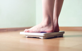 1200 woman stepping on scale article