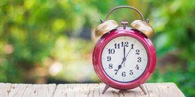 Red alarm clock on fooden floor 990x496 article