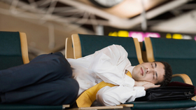 Businessman sleeping airport 78770981 small article