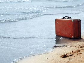 Suitcase on a beach photo courtesy npr article