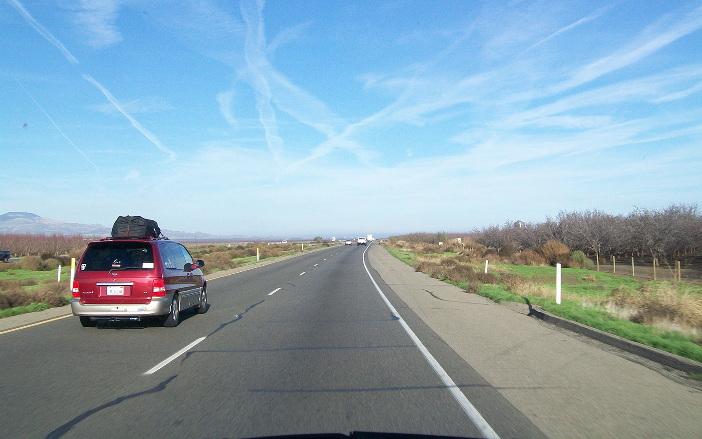 a red minivan travels on an open highway