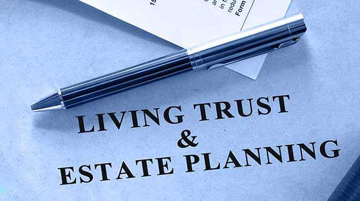 """Pen resting on document that says """"living trust and estate planning"""""""