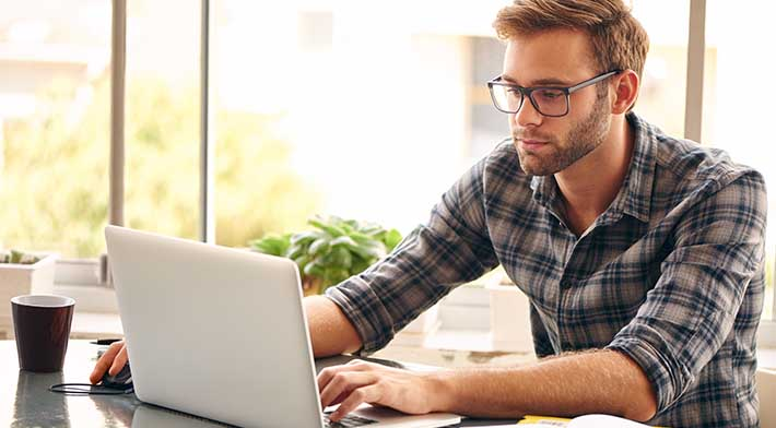 Millennial man with light stubble and large glasses uses mouse to scroll on laptop next to coffee cup in front of window