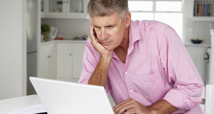 Older man in pink button down shirt hunches while sitting on white bed and looking at laptop