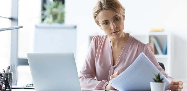 Businesswoman looking at a piece of paper next to her open laptop