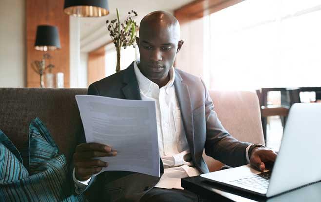 man sitting at desk looking at paperwork