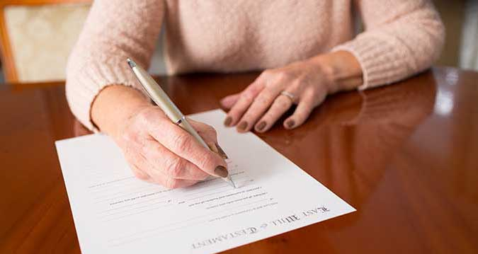 Woman in pink fluffy sweater signing document