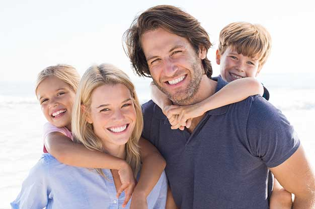 Smiling parents with two children on beach