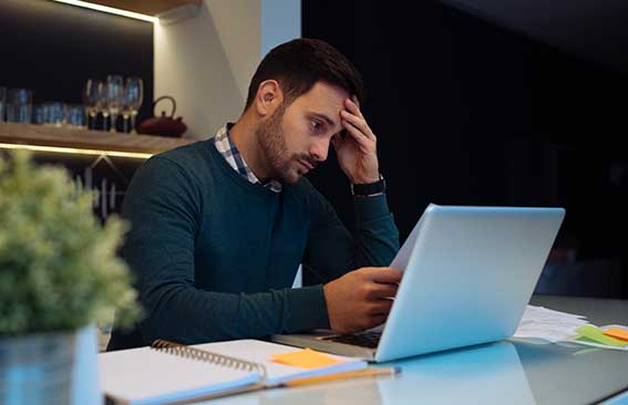 Man concernedly looking at laptop