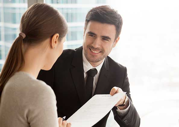 Man in suit handing document to woman