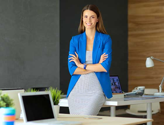 Woman in bright blue blazer leaning on desk