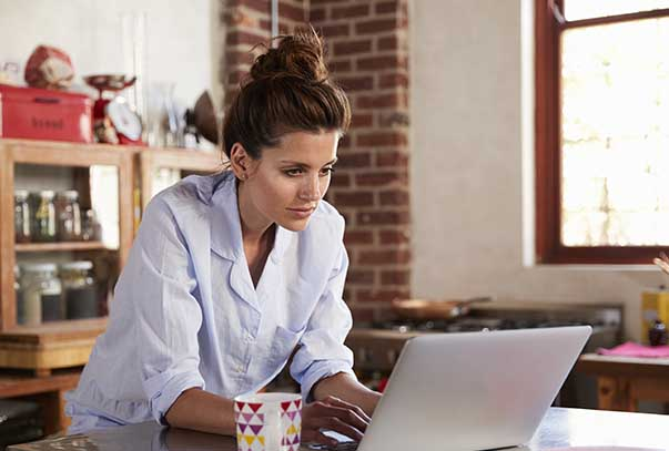 Woman types at laptop in kitchen