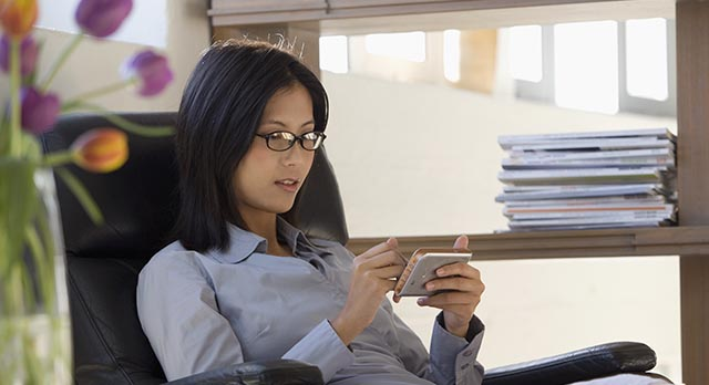 Woman in swivel chair looking at phone at desk