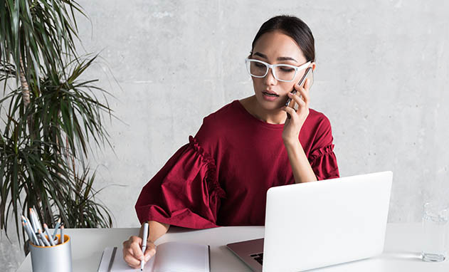 Woman in poofy red shirt writing in notebook while talking on phone at white desk