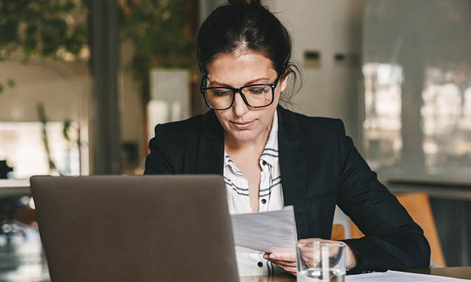Woman looking at paper in front of laptop