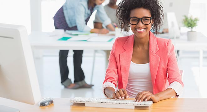 Smiling woman typing at laptop in pink blazer in office space